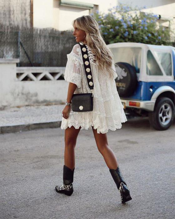 Vestido blanco de fiesta con botas texanas negras